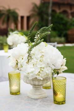 Crisp white hydrangeas placed in an urn are punctuated with flowers that have yet to bloom.