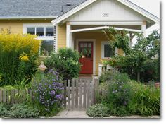 I love the white woodwork of the porch, and the yellow siding.  And the red door, of course!