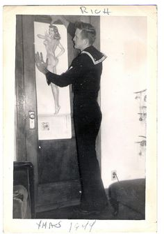 Sailor putting a pin up poster on the wal... This was the wallpaper of many men during ww2 ~