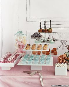 Breakfast at Tiffany's theme... front three-tiered stand holds rows of Tiffany box-inspired petits fours.  Glass jar of marshmallow sticks, white-and dark-chocolate-covered cherries in patterned paper cups, and lots of other goodies