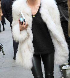 white faux fur coat on black