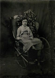 ca. 1865 - Unidentified deceased girl in wheelchair with cloaked attendant.