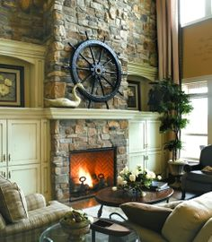 Giant black ship wheel on mantel shelf. Living room focal point.