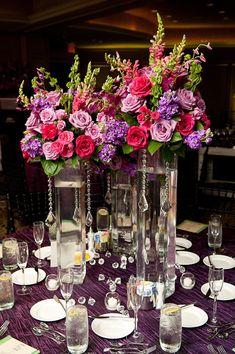 tabla de ajustes en la recepción - tres floreros de cristal altos con danging cristales de color rosa oscuro, rosa claro, púrpura y verde arreglos florales como centro de mesa y mantel morado - Foto de boda con sede en Houston fotógrafo Adam Nyholt