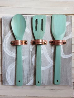 Make unique art for your kitchen with copper pipe straps and wooden utensils!