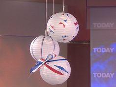 White paper lanterns decorated with red, white and blue ribbons.
