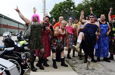 Members of a new charity called Steel Horsemen for Homeless Heroes take a break from shooting a group photo in their sundresses to wave at traffic Monday on Adams Street.