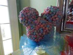 Mickey Mouse head made out of Dum Dum's and styrofoam. Displayed on a cake stand and wrapped with a bowtie.