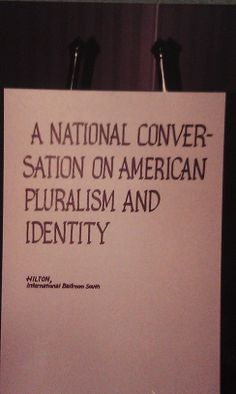 "Typical sign placed outside each session with the session title and room location. Text reads, ""A National Conversation on American Pluralism and Identity Hilton, International Ballroom South""."