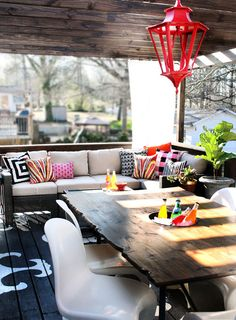 Lots to ♡ in this outdoor space: painted floor, wooden ceiling beams, cooler space in raw edged table, red metal lantern & color pop pillows!