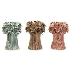 """Set of three ceramic candleholders with a bouquet design in multicolor finishes.   Product: 3 Piece candleholder setConstruction Material: CeramicColor: Blue, brown and pinkFeatures:  Resemble small bouquets of flowersChic addition to any décor  Accommodates: (1) Votive candle each - not includedDimensions: 7.5"""" H x 5.5"""" Diameter each"""