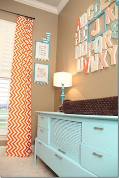 Sweet aqua, orange and brown nursery. Love the alphabet with the emphasis on baby's 'letter', the chevron stripe curtains and the painted aqua dresser!