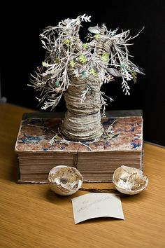 """Artworks cut and carved from books, mysteriously and anonymously left at libraries and other similar places. One note (attatched to a carving of a dragon emerging from an egg) reads: """"For @scotstorycenter - A gift in support of libraries, books, works, ideas..... Once upon a time there was a book and in the book was a nest and in the nest was an egg and in the egg was a dragon and in the dragon was a story....."""""""