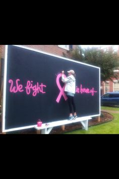 """Nu Chapter (The University of Alabama) put this chalkboard that says """"We fight in honor of..."""" on campus for students and faculty to write names on."""
