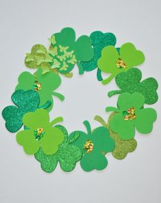 This emerald #shamrock craft makes a pretty #StPatricksDay #wreath for your home or classroom. #craftsforkids #fourleafclover #kuedkids