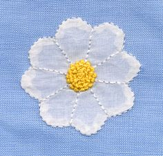 Cotton organdy daisy appliqued to blue linen with pinstitch.  Yellow center is French knots.  Featured in May 1991 Creative Needle Magazine.  Made by Trudy Horne.