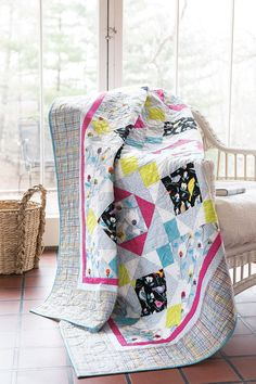 """The colorful birds in the fabric called out to designer Leigh Headington,""""Let me show off in a simple block. Economy would be nice!"""" The simple King's Crown block has a calming light blue, green and pink color scheme. Digital pattern and quilt kit available! Find this #quilt, A Balanced Economy, in Easy Quilts Fall '14."""