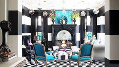 Kourtney Kardashian's Alice in Wonderland Living Room  // striped walls, globe-shaped pendants, checkered coffee table, blue armchairs
