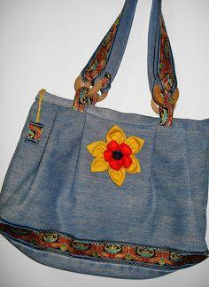 Confeccionada em velhos jeans, forrada, tem aplicação de ponto russo, argolas de madeira reaproveitadas de embalagem de perfume e enfeite /broche de flor de fuxico.