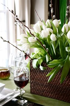 This spring centerpiece contains one bundle of pussy willows from Sams Club,  two bouquets of white tulips  from the grocery store and one small storage basket from Target.