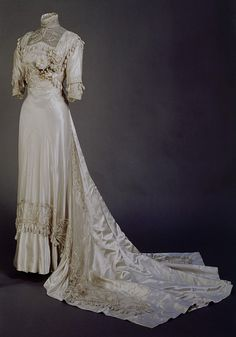 Early 1908 Wedding dress of ivory silk satin and with a sprig of artificial orange blossom. The dress is covered with matching net.  Applied silk rouleau in swooping and elongated Art Nouveau scrolls.