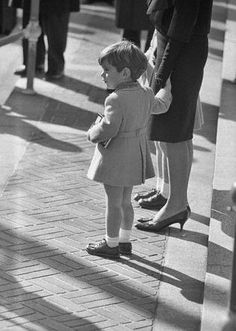 11/25/63 - John Jr. stands with his mother, outside St. Matthews Cathedral, following the funeral.