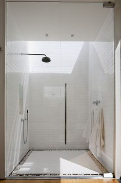 Subway tile in a running pattern, platform floor, drains hidden under rocks, overhead rainfall shower.  Very spa like!