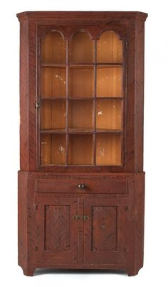 Sold $1,300 Pennsylvania painted two-part corner cupboard, ca. 1820, retaining a red and black feathered decoration, 80'' h., 38 1/2'' w.