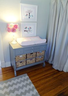 Vintage dresser turned changing table - love the how the bottom shelves were pulled and replaced with baskets! #nursery #storage #organization