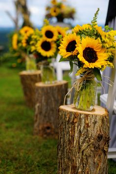 A charming aisle marker idea consisting of bouquets in mason jars consisting of Sunflowers and Solidago set on stumps. One of the benefits of DIY wedding flowers is that you can stay on budget and make the decorations uniquely you!