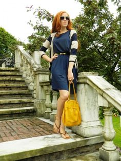 A blue dress with a striped cardi and yellow purse
