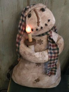 Grungy Primitive Snowman...an antique spool...with a lighted candle.