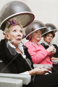 Group of Clients in Curlers Under Beauty Salon Hair Dryers. Royalty Free Stock Photo