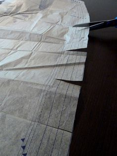 Snip the edges of the pattern and fold back to the size you need. Keeps all sizes available.