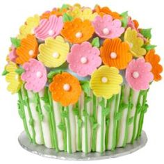 A beautiful bouquet of flowers conceals a giant cupcake cake. Use the Dimensions® Giant Cupcake Pan to bake a cupcake cake over 8 inches high and decorate it with bright, textured fondant flowers.