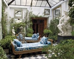 conservatory with tiled floor, marble sculpture and blue and white daybeds.