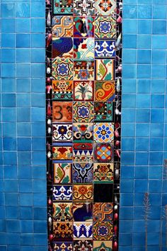 Outdoor shower with blue, black, gray and Mexican mosaic tiles.