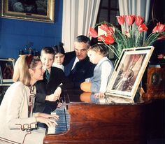 Princess Grace plays the piano for her family in the Waterloo room of the Palace of Monaco. Princess Stephanie sits on the piano with father Prince Rainier at her side whilst Princess Caroline of Hanover and Prince Albert II look on.