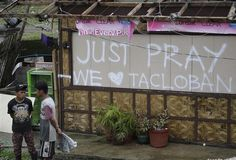 A graffiti is scribbled on a damaged home in Tacloban city, Leyte province, central Philippines, Tuesday, Nov. 12, 2013. Four days after Typhoon Haiyan devastated islands in the central Philippines, survivors are desperate for food and clamoring to be evacuated. (AP Photo/Bullit Marquez)