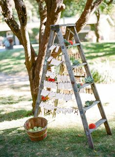 escort card display with wooden ladder, succulents and bushel basket of apples