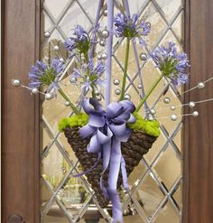 Wreath alternative - First Impressions    Inexpensive and easy to make, this festive basket greets guests and gives a hint of the night to come.    To make the arrangement: Start with a cone-shaped woven basket, and gently squeeze the sides to create an oval shape with a relatively flat back. Remove the metal chain, and replace it with ribbons to reach the desired height. Fill the cone with florist foam, securing it with floral tape. Soak the foam in water before filling the cone.    Top with reindeer moss, allowing it to loosely fall over the outer edges. Secure with florist pins. Insert fresh agapanthus flower stems (or any brightly colored, thick-stem medium bloom) into the foam, and fluff moss around as needed. For extra sparkle, insert whimsical silver balls.    Note: All florist supplies and glitter balls may be found at a local florist or crafts store.    First Impressions    Inexpensive and easy to make, this festive basket greets guests and gives a hint of the night to come.    To make the arrangement: Start with a cone-shaped woven basket, and gently squeeze the sides to create an oval shape with a relatively flat back. Remove the metal chain, and replace it with ribbons to reach the desired height. Fill the cone with florist foam, securing it with floral tape. Soak the foam in water before filling the cone.    Top with reindeer moss, allowing it to loosely fall over the outer edges. Secure with florist pins. Insert fresh agapanthus flower stems (or any brightly colored, thick-stem medium bloom) into the foam, and fluff moss around as needed. For extra sparkle, insert whimsical silver balls.    Note: All florist supplies and glitter balls may be found at a local florist or crafts store.    Gardman 14-inch Hanging Cone  Available at Lowe's