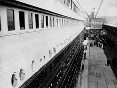 By the first class gangway a passenger paused to capture the dockside scene with the giant wall of Titanic's steel dwarfing the people on the ground. The second class gangway closes the view.