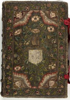 17th century embroidered Canvas book, pictorial angel and floral motif  with two red ribbons.