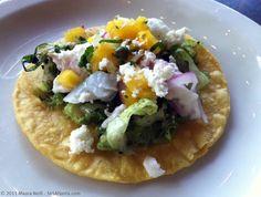 Ceviche tostada - crispy corn tortilla, guacamole, grilled lettuce, shrimp and fish ceviche, yellow pico de gallo, queso fresco
