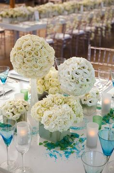 White pomanders of roses, ranunculus and hydrangeas are arranged at varying heights on each square table.