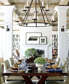 Exposed beams, white bookshelves, flowers, dark wood table. #diningroom