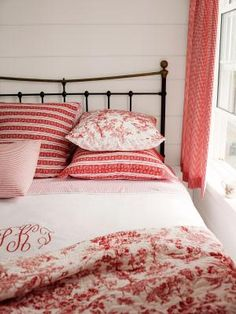 Soften a wrought-iron bed by decorating with a mixture of red toile and ticking linens. Looks so cozy! #decoratingtips
