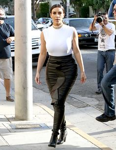 Kim Kardashian  a tight leather pencil skirt by Givenchy, high-collared Lanvin top and Tamara Mellon's black leather legging boots.