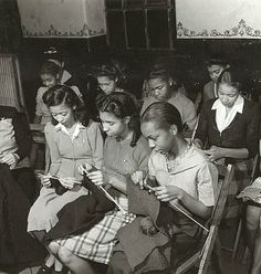 Young African-American women knitting bundles for bluejackets, during wartime in a Louisville, Kentucky church rectory.