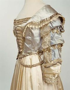 """Dress side detail. This dress was worn by Sarah Coke, who lived at Brookhill Hall, Pinxton, Derbyshire, at a fancydress ball in Nottingham in 1826. It was Sarah's """"coming out"""" ball, her first social event as an adult, and the dress was supposed to represent the fashion of Charles II's time, and she wore her hair in ringlets, adorned with white ostrich feathers."""